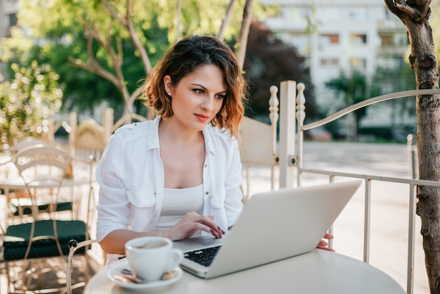 Schöne junge frau, die draußen vom café arbeitet.
