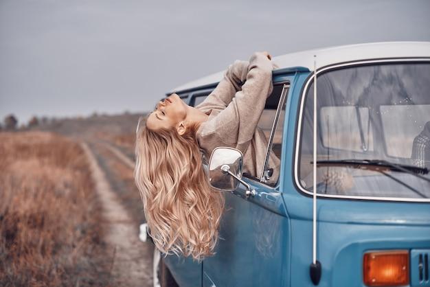 Schöne junge frau, die durch ein fenster schaut, während sie einen roadtrip im minivan genießt?
