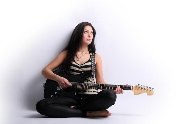 Schöne junge frau, die e-gitarre spielt