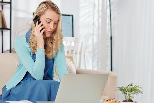 Schöne junge frau, die e-mail auf laptop liest und am telefon spricht, wenn sie von zu hause aus arbeiten, weil sie sperren