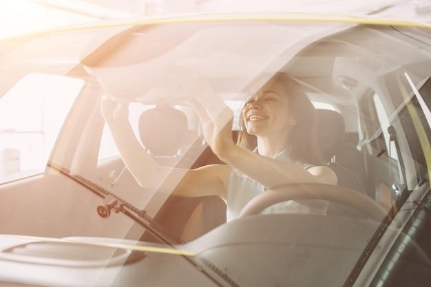 Schöne junge frau, die ein auto am autohaus kauft. weibliches modell, das innerhalb des fahrzeugs im ausstellungsraum sitzt.