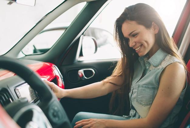 Schöne junge frau, die ein auto am autohaus kauft. weibliches modell sitzt sitzt im innenraum des autos