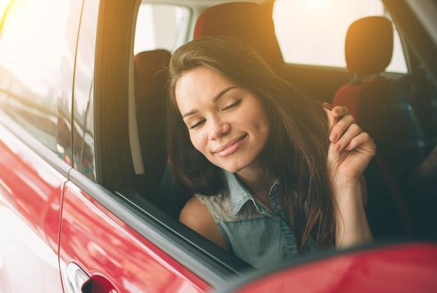 Schöne junge frau, die ein auto am autohaus kauft