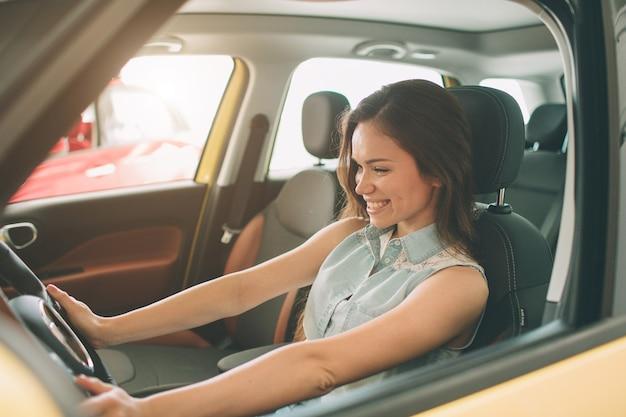 Schöne junge frau, die ein auto am autohaus kauft.