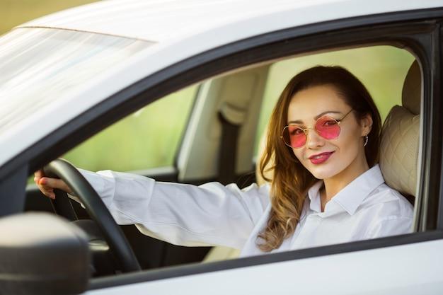Schöne junge frau, die ein auto fährt