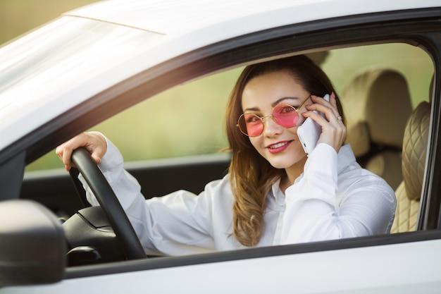 Schöne junge frau, die ein auto mit einem handy fährt