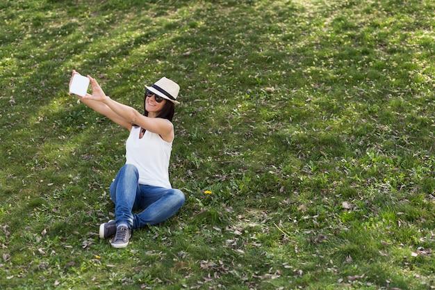 Schöne junge frau, die ein bild mit einer tablette über grünem hintergrund macht. lebensstil.
