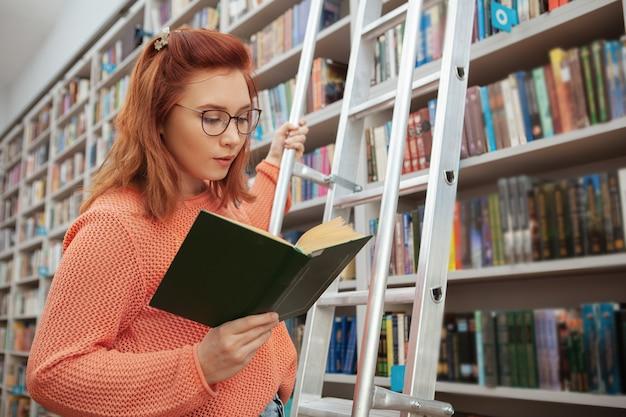 Schöne junge frau, die ein buch an der bibliothek liest, die auf der leiter steht