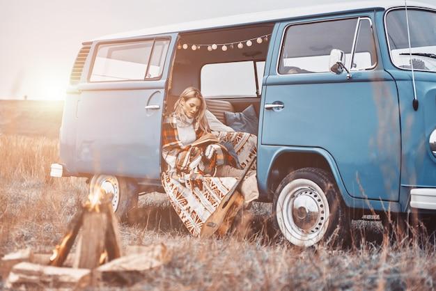 Schöne junge frau, die ein buch liest und lächelt, während sie zeit im retro-minivan verbringt