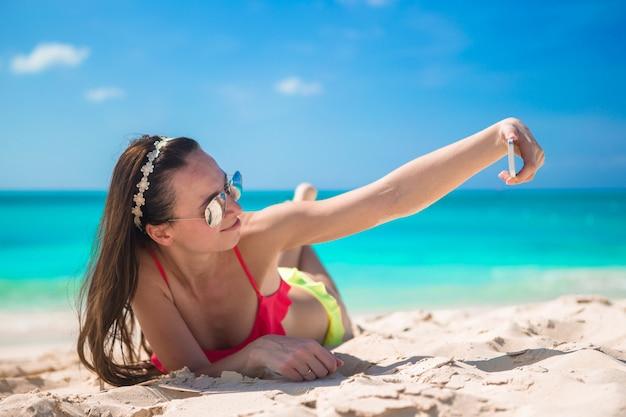 Schöne junge frau, die ein foto auf tropischem strand sich macht