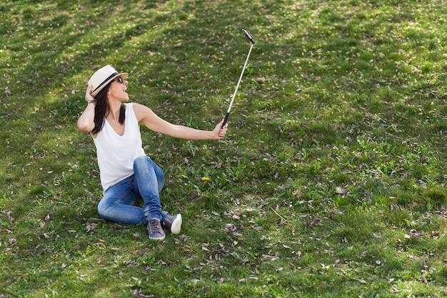 Schöne junge frau, die ein foto mit einem selfie-stock macht. spaß haben konzept. sie trägt hut und sonnenbrille. lebensstil