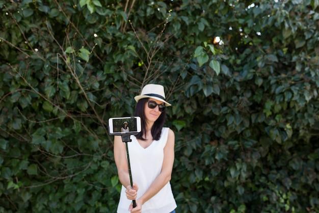 Schöne junge frau, die ein foto mit einem selfie-stock macht. spaß haben konzept. sie trägt hut und sonnenbrille.