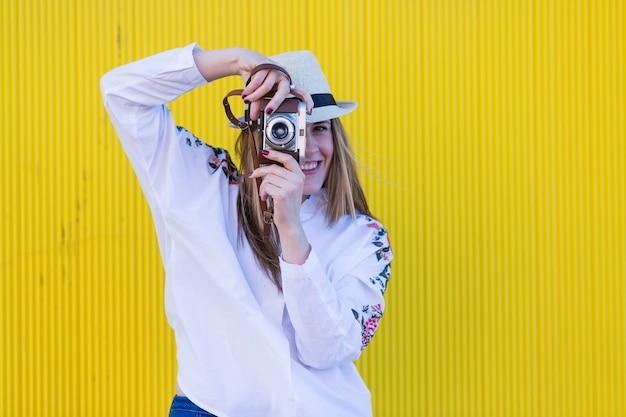 Schöne junge frau, die ein foto mit und alter weinlesekamera gelbwand macht
