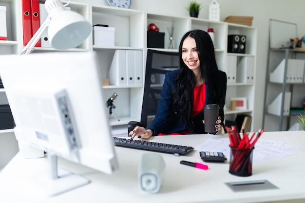 Schöne junge frau, die ein glas in ihrer hand mit kaffee hält und text auf der tastatur, sitzend auf einem stuhl im büro am tisch schreibt.