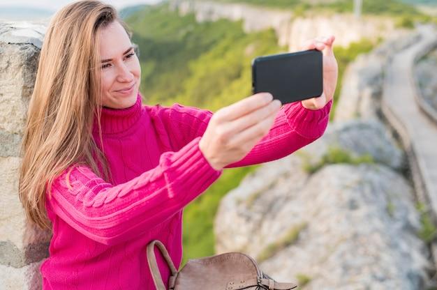 Schöne junge frau, die ein selfie draußen nimmt