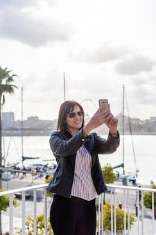 Schöne junge frau, die ein selfie mit ihrem handy in màlaga, ein sonniger tag macht
