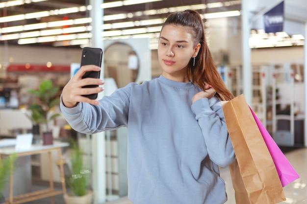 Schöne junge frau, die ein selfie mit ihrem smartphone beim einkaufen im einkaufszentrum nimmt