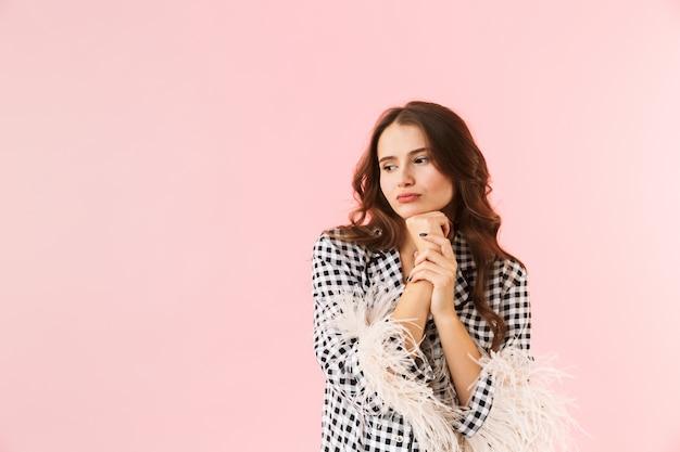 Schöne junge frau, die eine jacke trägt, die lokal über rosa hintergrund steht und aufwirft