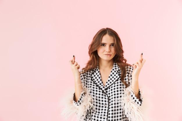 Schöne junge frau, die eine jacke trägt, die lokal über rosa hintergrund steht und die finger für viel glück gekreuzt hält