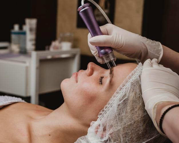 Schöne junge frau, die eine kosmetische behandlung am wellness-center hat