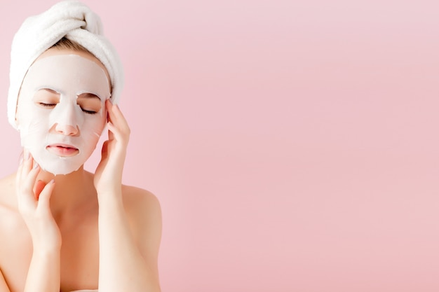 Schöne junge frau, die eine kosmetische gewebemaske auf gesicht anwendet