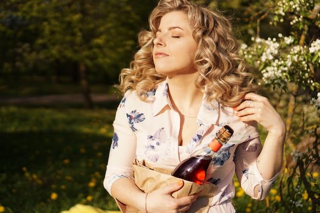 Schöne junge frau, die eine leere flasche wein beim mittagessen im freien hält. picknick im park mit grünem gras