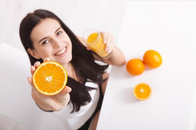 Schöne junge frau, die eine orange in ihrer hand hält und lächelt
