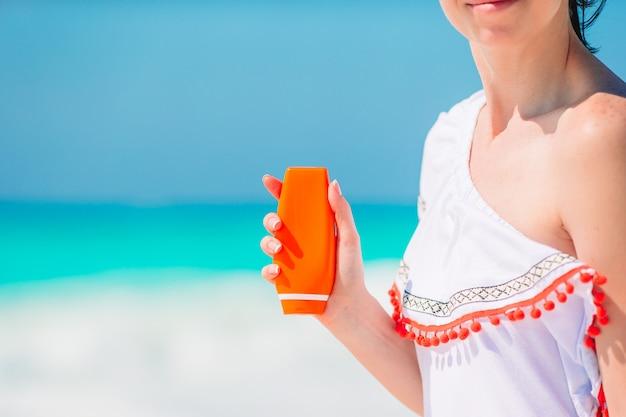 Schöne junge frau, die eine sonnencreme am tropischen strand hält