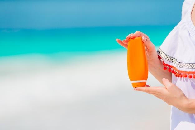 Schöne junge frau, die eine sonnencreme auf tropischem strandhintergrund hält
