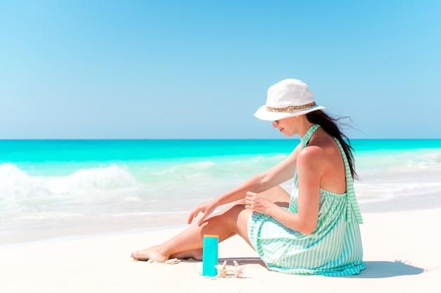 Schöne junge frau, die eine sonnencreme hält, die am strand liegt