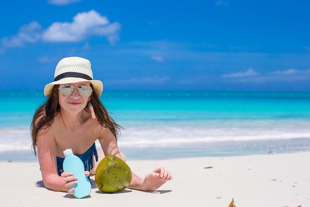 Schöne junge frau, die eine sonnencreme liegt auf tropischem strand hält