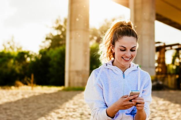 Schöne junge frau, die eine textnachricht auf dem strand sendet