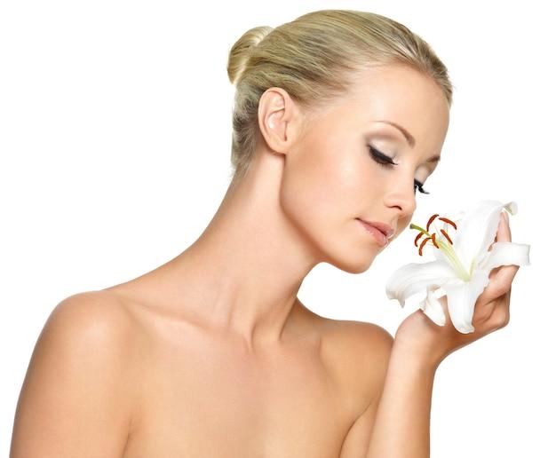 Schöne junge frau, die eine weiße lilie im gesicht hält, lokalisiert auf weiß