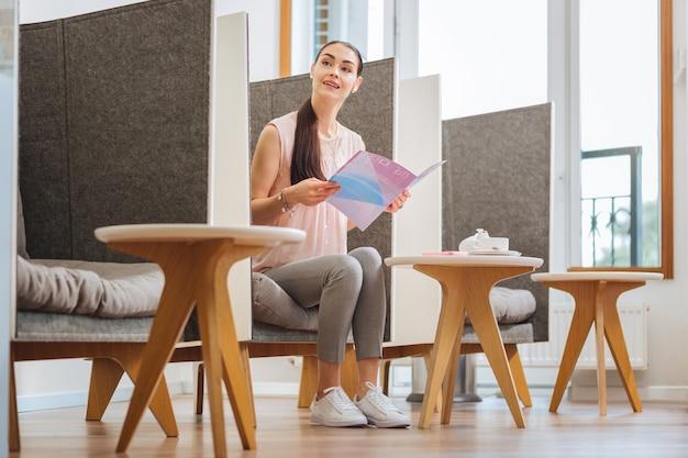 Schöne junge frau, die eine zeitschrift liest, während sie auf ihren termin wartet