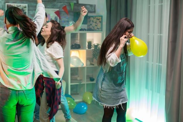 Schöne junge frau, die einen ballon hält, während sie auf einer party mit lauter musik ein gespräch über ihr telefon führt.