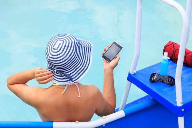 Schöne junge frau, die einen blau-weiß gestreiften sonnenhut trägt und im swimmingpool sitzt und sich entspannt. attraktive dame beim sonnenbaden und genießen im offenen wasser an einem sonnigen tag enjoying