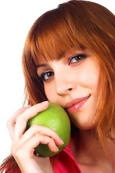 Schöne junge frau, die einen grünen apfel anhält