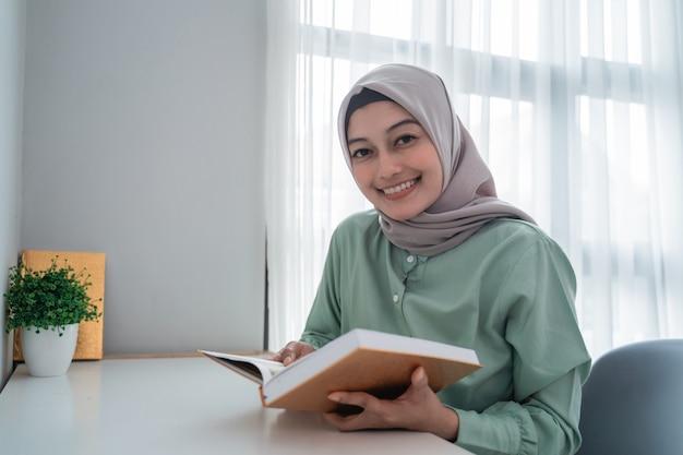 Schöne junge frau, die einen lächelnden hijab trägt, der das heilige buch des korans hält