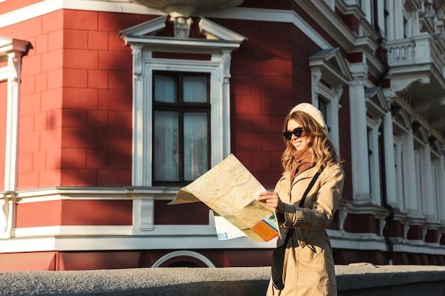 Schöne junge frau, die einen mantel trägt, der draußen geht und stadtplan hält