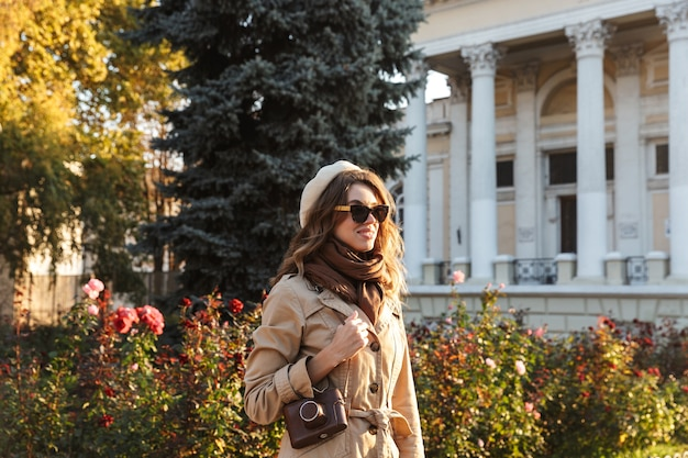 Schöne junge frau, die einen mantel trägt, der draußen unter verwendung der fotokamera geht