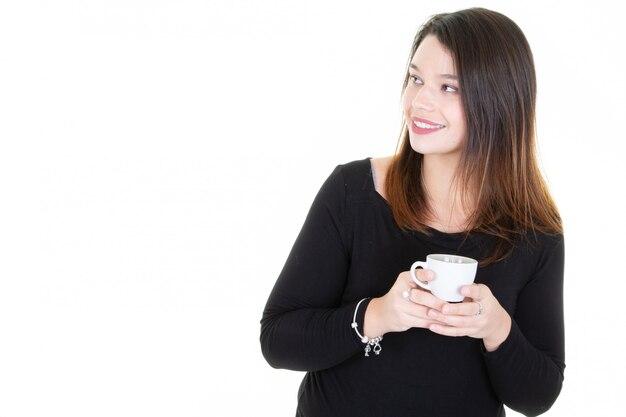 Schöne junge frau, die einen tasse kaffee genießt und seite im kopienraumweiß schaut