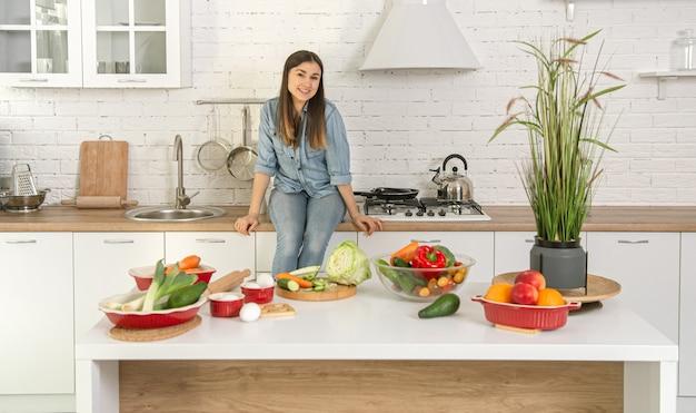 Schöne junge frau, die einen vegetarischen salat aus verschiedenen gemüsen auf dem hintergrund des kücheninnenraums in hellen farben vorbereitet.