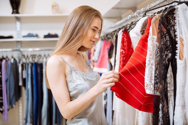Schöne junge frau, die einkaufen und kleidung im geschäft wählt