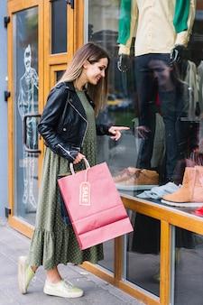 Schöne junge frau, die einkaufstasche zeigt finger auf fensteranzeige hält