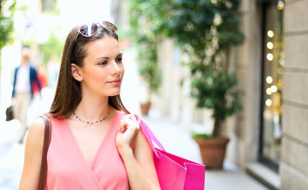 Schöne junge frau, die einkaufstaschen hält und in ein stadtzentrum im freien geht