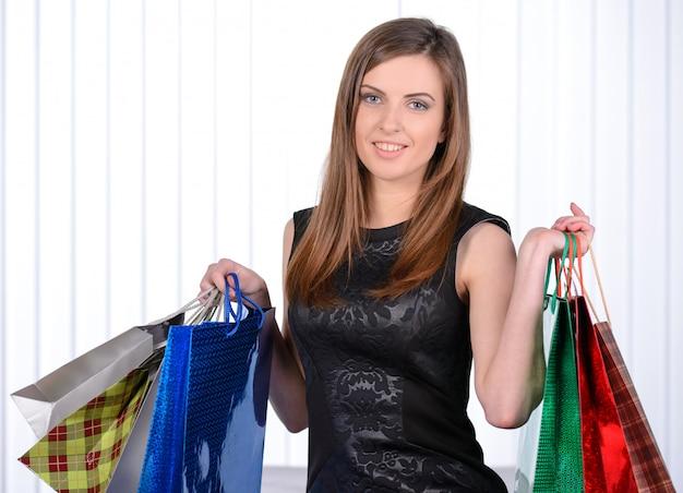 Schöne junge frau, die einkaufstaschen hält.
