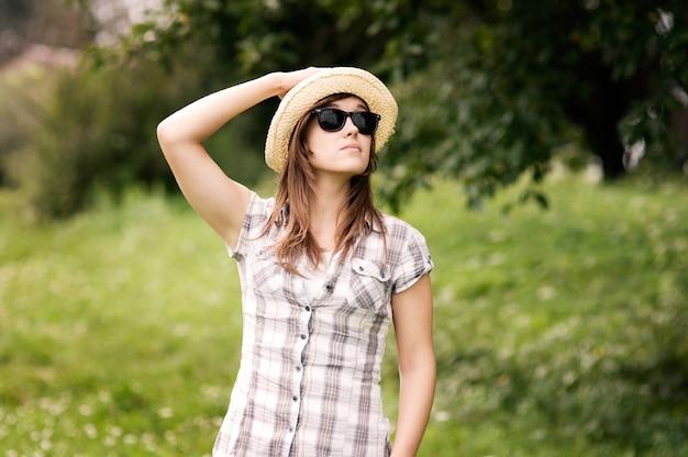 Schöne junge frau, die fedorahut und sonnenbrille trägt