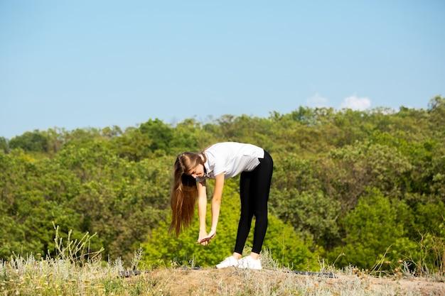 Schöne junge frau, die flexibilität im freien trainiert