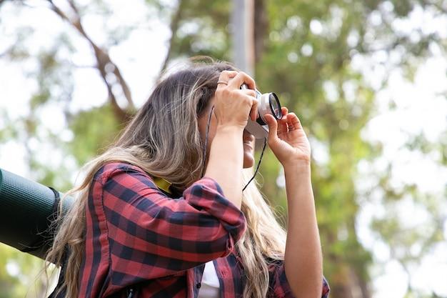 Schöne junge frau, die foto und wandern mit rucksack nimmt. aufgeregte weibliche reisende, die landschaft schießt und lächelt. backpacking tourismus, abenteuer und sommerurlaub konzept