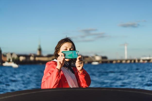 Schöne junge frau, die fotos auf einem smartphone macht
